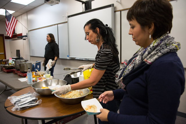 Todd English P.U.B. executive chef Jean Paul Labadie, left, is assisted by Carol Lanata, center, and Communities In Schools of Nevada Academy Director Melissa Lemon, right, during a food demonstra ...