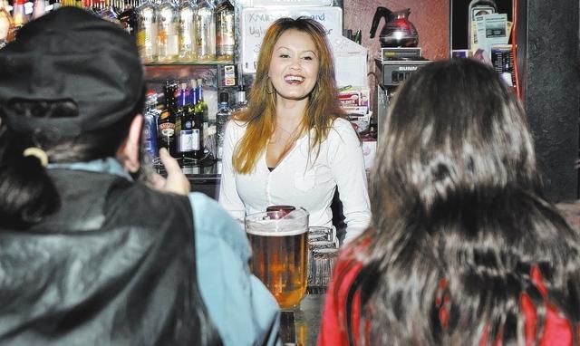 "Bartender Sondra Mundo talks with customers Robin ""Tennessee"" Horton and his wife, Natalie, at Double Shots Bar. (Bill Hughes/View)"