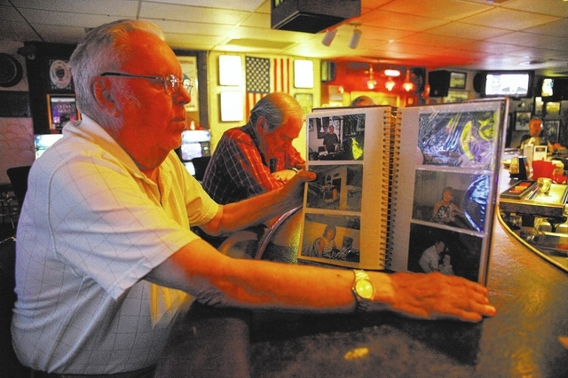 Jack's Place co-owner Bruce Wagner looks at a photo album capturing the bar's past. (Robert Winn/View)