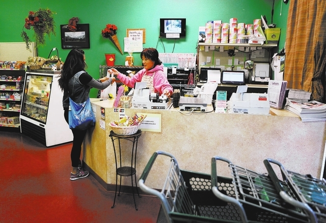 Shopper Vianca Altura takes her purchases from cashier Yoshie Meyer at Japan Creek Market, 9310 S. Eastern Ave., which sells authentic Japanese foods, baked goods and products. (Ronda Churchill/View)