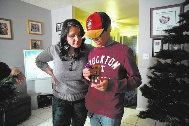 Alexis Newell watches her son Justice, 11, check his blood sugar level Dec. 10 at their Las Vegas home. Justice was diagnosed with Type 1 diabetes when he was 6. The family recently returned from  ...