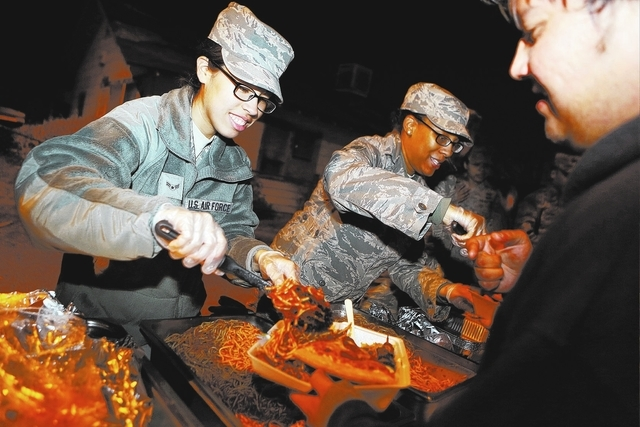 U.S. Air Force Airman 1st Class Evelisse Cortes, left, and Senior Airman Amber McClenney serve spaghetti to the homeless and others in need Nov. 25 on the corner of McWilliams Avenue and G Street. ...