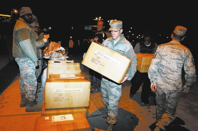 U.S. Air Force Tech Sgt. Ryan Lucas unloads a box of fleece blankets during a gathering to feed the homeless and others in need Nov. 25 on the corner of McWilliams Avenue and G Street. (Ronda Chur ...