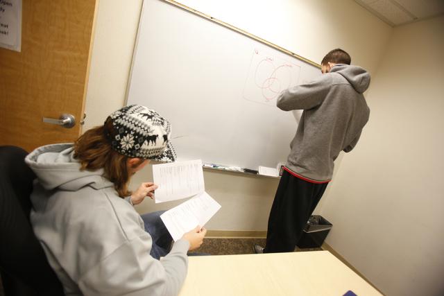 Senior and UNLV Baseball player Robert Johnson, center, helps tutor senior Runnin' Rebels basketball player Carlos Lopez-Sosa for a final exam in Fundamentals of College Mathematics has he draws a ...
