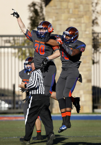 Dylan Weldon (30) of Bishop Gorman celebrates with teammate Armand Perry (13) after Weldon made an interception against Palo Verde during the Sunset Region championship football game at Bishop Gor ...
