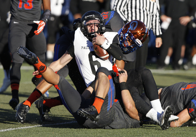 Parker Rost (6) of Palo Verde gets tackled by Bishop Gorman players during the Sunset Region championship football game at Bishop Gorman High School in Las Vegas Saturday, Nov. 30, 2013. (John Loc ...