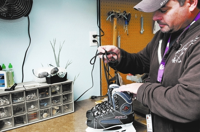 Clark County parks recreation specialist Al Galvin, ties the shoelaces on a new pair of ice skates at Sunset Park, 2601 E. Sunset Road, in Las Vegas, Tuesday, Dec. 3, 2013. The park is hosting Sun ...