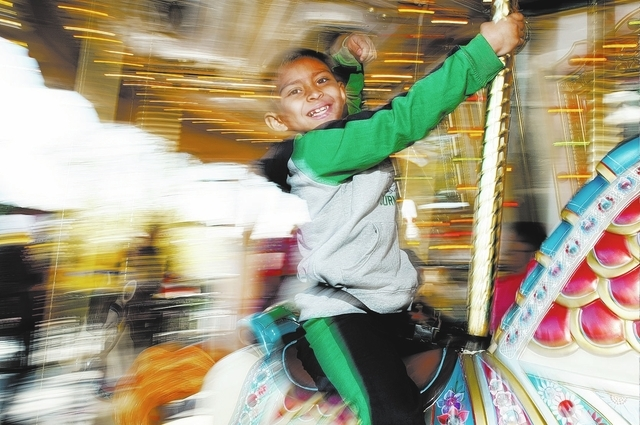First grade student Jeffree Aviles, 6, rides the carousel with his classmates from Ruby Thomas Elementary School during their visit to Magical Forest at Opportunity Village in Las Vegas, Monday, D ...