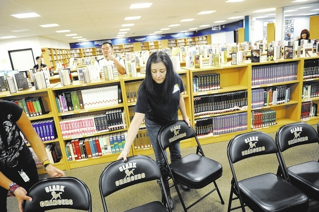 Elaine LeVecci, a volunteer from Capital One, helps to setup chairs at the Clark High School Library in Las Vegas on Tuesday, November 12, 2013. Clark High School received a grant from Capitol One ...