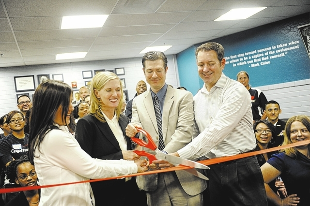 From left, Librarian Tirsa Ceniza, Principal Jill Pendleton, Chief Student Achievement Officer Dr. Mike Barton, and Paul Keagle, VP Operations at Capital One, open the redesigned Clark High School ...