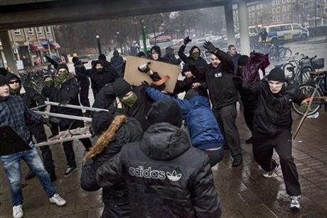 Right-wing extremists, background, clash with anti-nazi demonstrators in the Stockholm suburb of Karrtorp, Sweden, Sunday, Dec. 15, 2013. There were several injuries and dozens were arrested. (AP  ...
