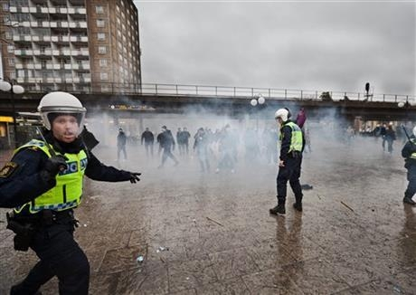 Police try to stop right-wing extremists from attacking an anti-nazi demonstration in the Stockholm suburb of Karrtorp, Sweden, Sunday, Dec. 15, 2013. There were several injuries and dozens were a ...