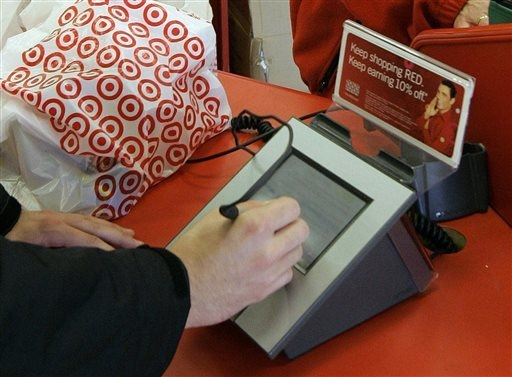 In this Jan. 18, 2008 file photo, a customer signs his credit card receipt at a Target store in Tallahassee, Fla. The U.S. is the juiciest target for hackers hunting credit card information. And e ...