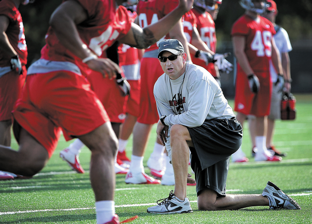 UNLV's defensive coordinator Tim Hauck works with players during football practice at Rebel Park at UNLV on Tuesday, August 6, 2013. Hauck, a retire NFL player, is also head coach Bobby Hauck's yo ...