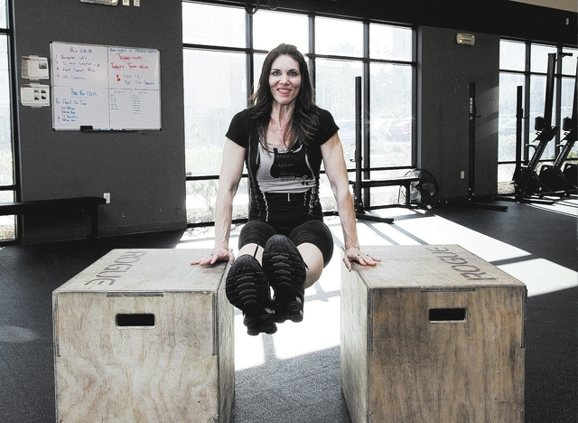 Trainer Laura Salcedo demonstrates the modified finishing position for the L-Sit exercise at CrossFit Mountain's Edge on Tuesday, Nov. 26, 2013. (Justin Yurkanin/Las Vegas Review-Journal)