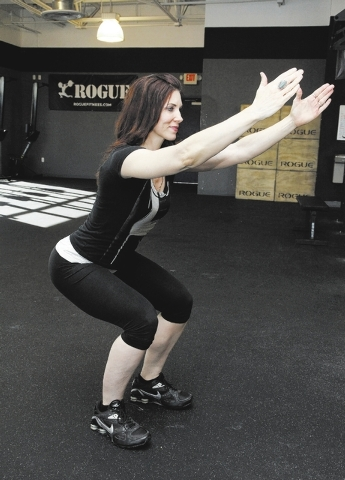 Trainer Laura Salcedo demonstrates the starting position for the jumping squat  exercise at CrossFit Mountain's Edge on Tuesday, Nov. 26, 2013. (Justin Yurkanin/Las Vegas Review-Journal)