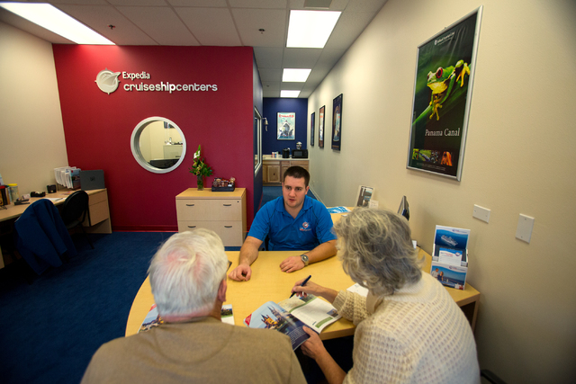 Expedia Cruise Ship Centers manager Morgan Maurer, center, talks with Gene and Dee Tress about European river cruises Thursday, Dec. 12, 2013 at the 1930 Village Center Circle office. The brick an ...