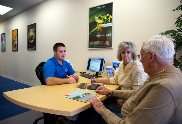 Expedia Cruise Ship Centers manager Morgan Maurer, left, talks with Dee and Gene Tress about European river cruises Thursday, Dec. 12, 2013 at the 1930 Village Center Circle office. The brick and  ...