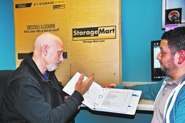 StorageMart LLP's CMO Tron Jordheim, left, and advertising coordinator Julio Montes review vendor records. StorageMart is headquartered in Columbia, Mo. (Courtesy StorageMart LLP)