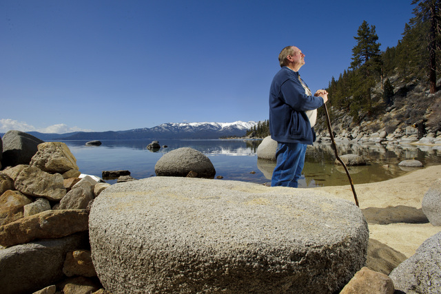 Retired U.S. Forest Service hydrologist Larry Schmidt stands in front of a granite slab in 2010 that Nevada historians believe was used by Mark Twain as a table for meals and card games on the sho ...