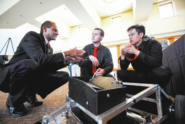 Rama Venkat, Interim Dean of the College of Engineering, talks with Jared Peterson, center, and Jameson Lee, who's project is the Autonomous Brass Collecting Rover during the Senior Design Competi ...