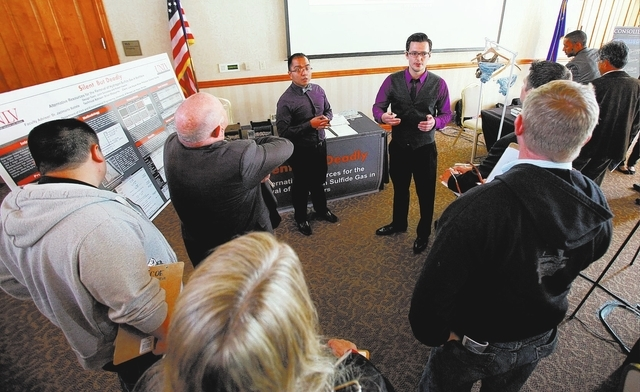 """Robert Kazarin, right, with John Gonzales, present their project """"Silent, but Deadly"""" to judges and attendees during the Senior Design Competition at the Foundations Building at the Univ ..."""