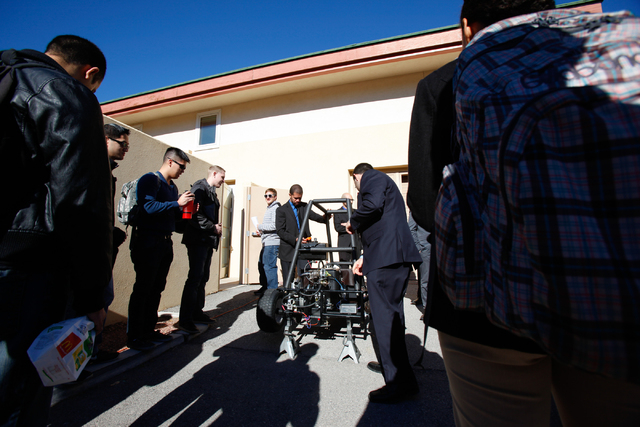 """Sammy Elshaal, center right, Leandro Moreira, left, of the""""Electric Generating Turbo"""" project, talk to attendees during the Senior Design Competition at the Foundations Building at the U ..."""
