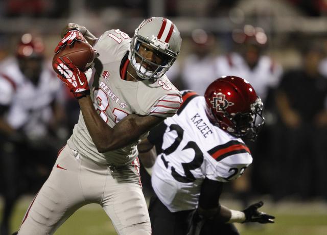 UNLV player Devante Davis makes a catch before scoring a touchdown over Damontae Kazee of the Aztecs at Sam Boyd Stadium in Las Vegas Saturday, Nov. 30, 2013. (John Locher/Las Vegas Review-Journal)