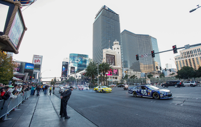 NASCAR Sprint Cup champion Jimmie Johnson heads down the Las Vegas Strip in his No. 48 car, during the Victory Lap event of the NASCAR Championship Week, outside of the Paris and Bellagio in Las V ...