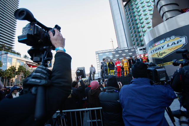Members of the news media film and take photos of the top 13 NASCAR Sprint Cup drivers at the Victory Lap event of the NASCAR Championship Week, outside of Planet Hollywood in Las Vegas on Thursda ...