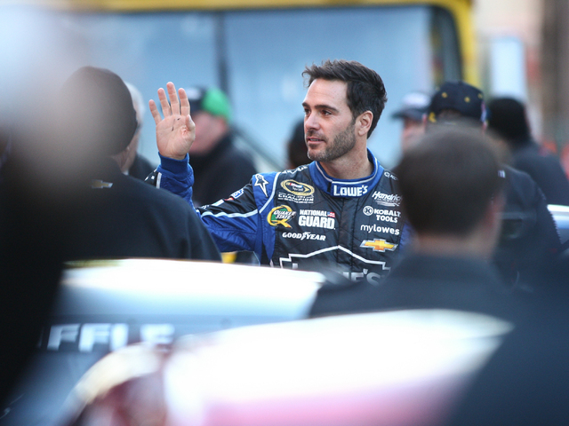 NASCAR Sprint Cup champion Jimmie Johnson waves to fans during the Victory Lap event of the NASCAR Championship Week, outside of the Paris and Bellagio in Las Vegas on Thursday, Dec. 5, 2013. (Cha ...
