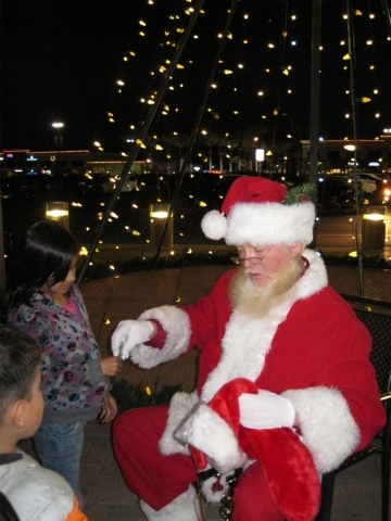 Santa Claus hands out candy to children during the event. (Special to View)