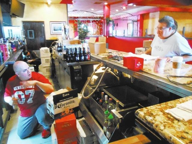 Jason Watkins stocks Coronita Extra in an under-the-counter refrigerator as Viva Mercado's owner/operator Bobby Mercado oversees the bar setup Nov. 14 at his new location in Village Square, 9400 ...