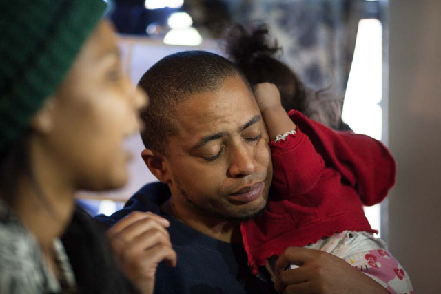 Michael Howard takes a quiet moment with his 9-month old daughter Keianah while giving interviews to local news crews with his partner, Octavia Haney, in their east Las Vegas apartment Friday, Dec ...