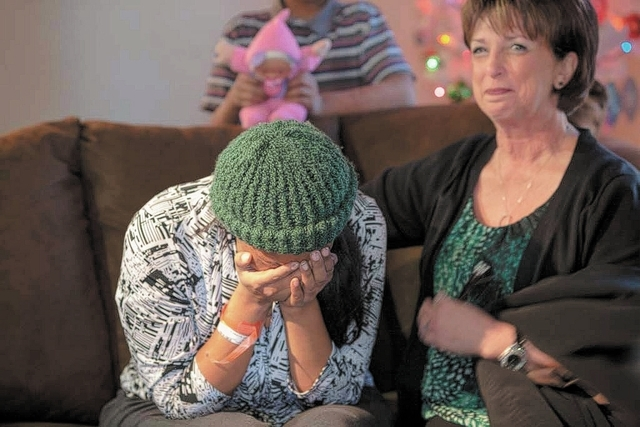 Walker Furniture Marketing Director, Patti Gerace, comforts Octavia Haney as she is overcome with emotion after receiving a full home of furniture in her family's east Las Vegas apartment Friday,  ...