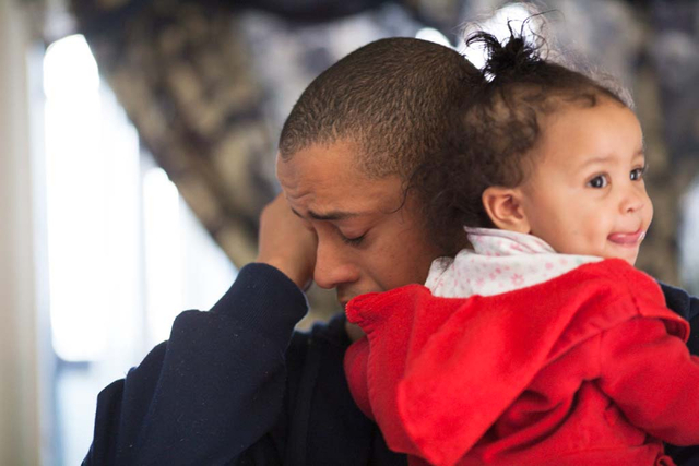Michael Howard, holding his daughter Keianah (9 mo.s), is overcome with emotion after receiving a home full of new furniture in his family's east Las Vegas apartment Friday, Dec. 13, 2013. Every y ...
