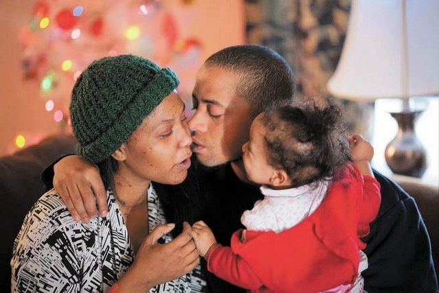 Michael Howard gives his partner, Octavia Haney, a kiss while he holds their 9-month-old daughter, Keianah in their east Las Vegas apartment on Friday, Dec. 13, 2013. Every year Walker Furniture d ...