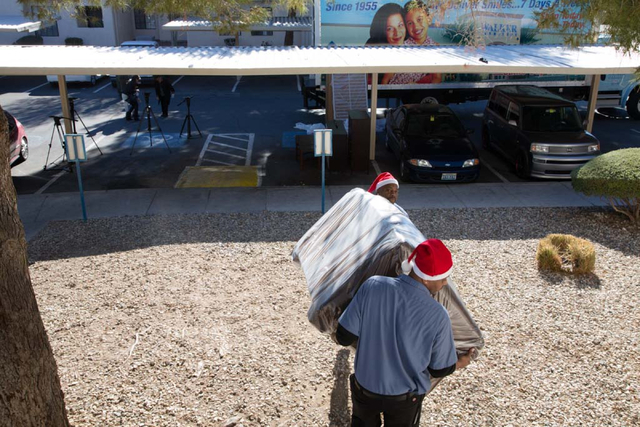 Walker delivery men, Joseph Wayman (facing camera) and Clarence McQaurtres, walk a new sofa into the home of Michael Howard and Octavia Haney in east Las Vegas on Friday, Dec. 13, 2013. Every year ...