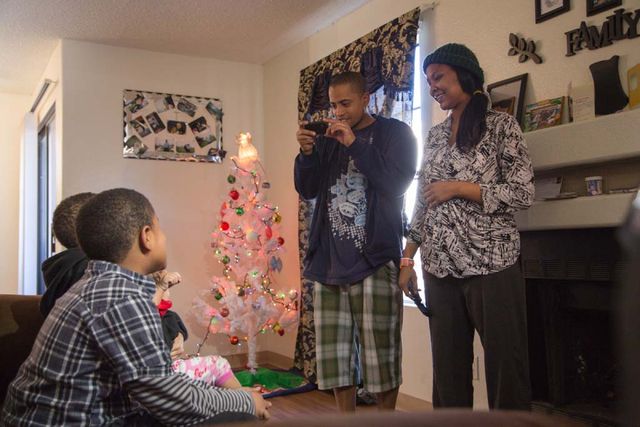 """Michael Howard and Octavia Haney take photos of their children as they sit on their new sofa in their east Las Vegas apartment on Friday, Dec. 13, 2013. Every year Walker Furniture does a """"Ho ..."""