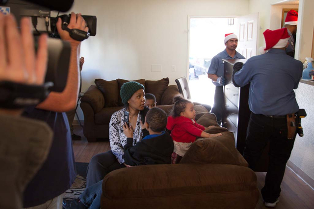 Octavia Haney watches on with her children as Van Cha, rear, and Luis Arellanes carry in a new dresser to her family's east Las Vegas apartment home on Friday, Dec. 13, 2013. Every year Walker Fur ...