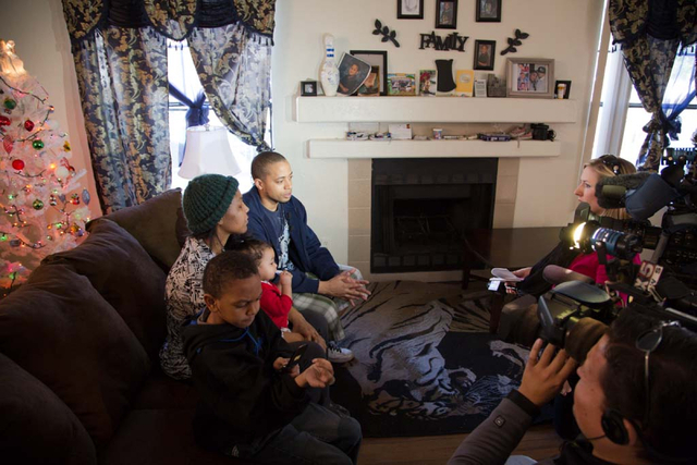 Octavia Haney holds her daughter 9-month-old daughter Keianah while giving interviews to local television news crews with her partner Michael Howard and their son, Byron (6), in their east Las Veg ...