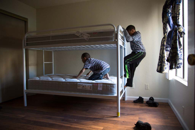 """Byron Howard, 6, and his brother Deandre, 8, play their new bunk beds in their family's east Las Vegas apartment on Friday, Dec. 13, 2013. Every year Walker Furniture does a """"Home for the Hol ..."""