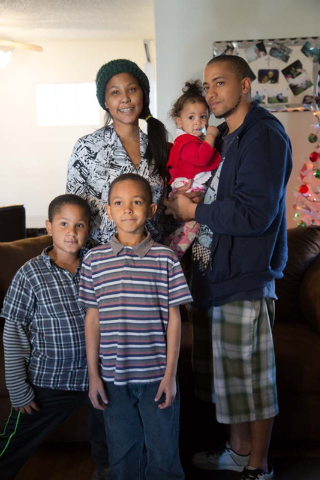 Octavia Haney and Michael Howard, pose for a portrait in front of their new sofa with their children, Deandre, 8,  Byron, 6, and Keianah 9 months, in their east Las Vegas home on Friday, Dec. 13,  ...