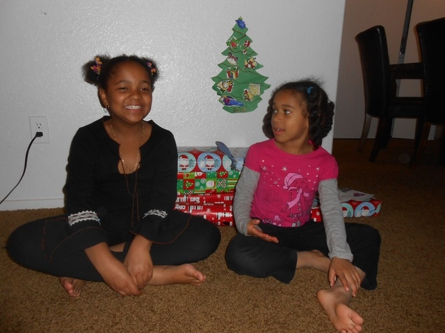 Sharlize Flagg, 8, and her sister Heidi, 5, talk about getting beds to sleep in from Walker Furniture's Home for the Holidays program Dec. 18 in their apartment near Summerlin. Behind them is the  ...