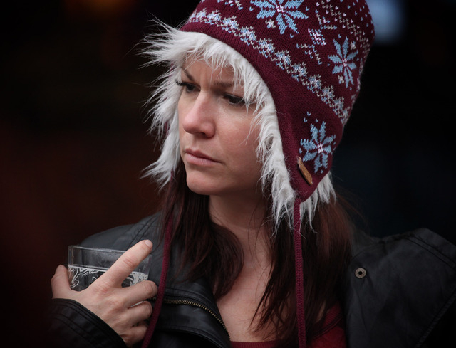 Tawny Shoemaker of Las Vegas dons a hat to keep warm while watching a street artist perform at the Fremont Street Experience in Las Vegas Wednesday, Oct. 9, 2013. Temperatures are expected to dip  ...
