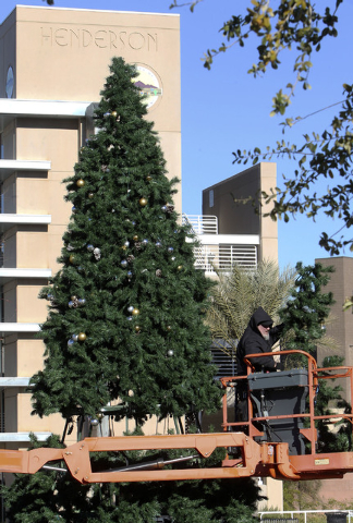 Bundled up against  the cold, Mike Harbin, of Rhino Strategies, assembles a Christmas tree display on the Civic Center plaza in downtown Henderson, Wednesday, Dec. 4, 2013.   (Jerry Henkel/Las Veg ...