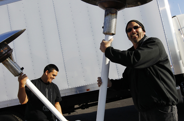 Anthony Tellez, left, and Richard Femenella move heaters into place in preparation for a cold First Friday event in Las Vegas on Dec. 6, 2013. (Jason Bean/Las Vegas Review-Journal)