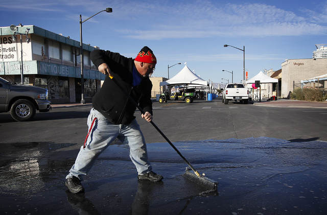George Heinrich sweeps water off the road to prevent ice build up in preparation for a cold First Friday event in Las Vegas on Dec. 6, 2013. (Jason Bean/Las Vegas Review-Journal)