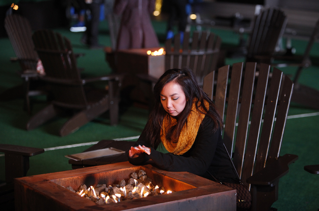 Erica Santos warms up by a fire near the ice skating rink at the Cosmopolitan Las Vegas on Thursday. The rink will be open through Jan. 5. (John Locher/Las Vegas Review-Journal)