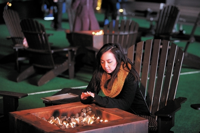 Erica Santos warms up by a fire near the ice skating rink at the Cosmopolitan Las Vegas on Thursday. There is a chance of snow flurries, rain and freezing temperatures in the Las Vegas Valley this ...